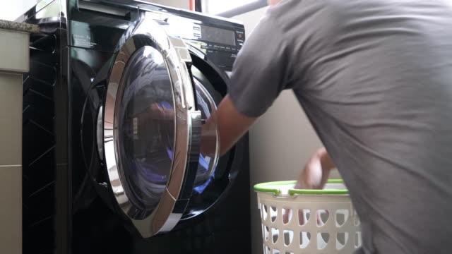 tägliche hausarbeit : mann-wäscherei wie zu hause fühlen. - waschmaschine stock-videos und b-roll-filmmaterial