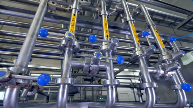 Dairy factory pipes with blue stop handles. video