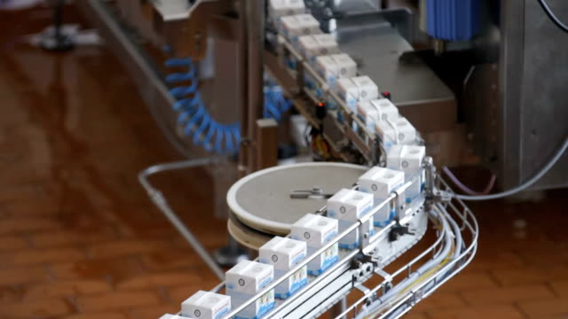 Dairy products in tetra packaging Milk package conveyor. Dairy products in tetra packaging are moving along the conveyor at a dairy factory. conveyor belt stock videos & royalty-free footage