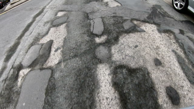 4k: damaged road with many potholes - driving over, looking down - foro video stock e b–roll