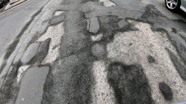 4k: damaged road with many potholes - driving over, looking down - dziura filmów i materiałów b-roll