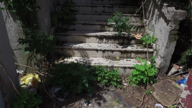 Damaged stairs and wall of abandoned domestic residential house or building with hole without windows and doors full of garbage an junk view from town to up