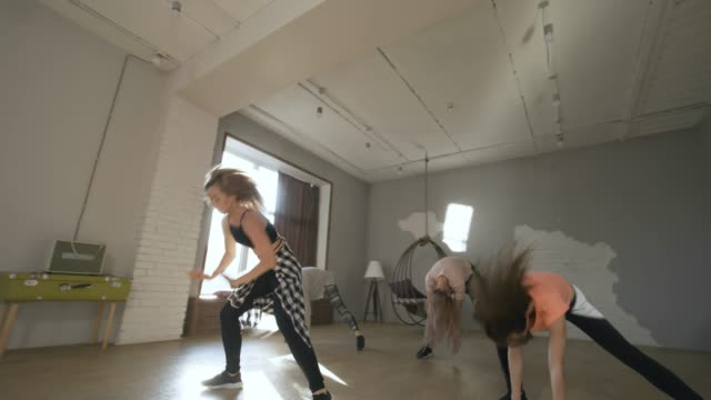 Dance Instructor and Group of Women Practicing Moves Tracking shot of young female dance instructor and group of women practicing choreography routine in studio on sunny day dance studio stock videos & royalty-free footage