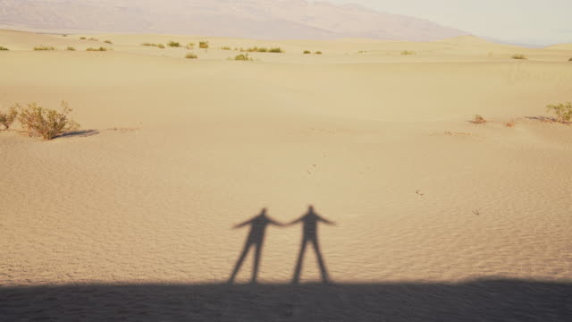 vídeos de stock e filmes b-roll de dance of shadows. two friends who are not presented in the video themselves but only their shadows dancing on the sand dunes at mesquite flats, death valley, california. - parque nacional do vale da morte