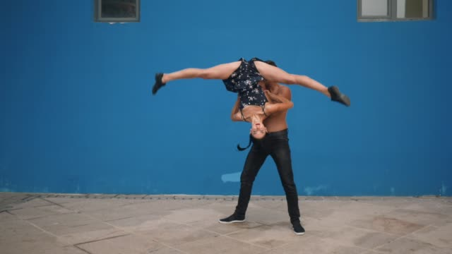 Dance partners demonstrating sensual dance pattern with acrobatics in slow motion on blue background. Dancing outdoors in the city