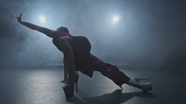 Dancer at smoky stage with spotlights. Woman performing modern dance in 4K, UHD Professional dancer at smoky stage with spotlights. Woman performing modern dance. Silhouette of female. 4K, UHD dance studio stock videos & royalty-free footage
