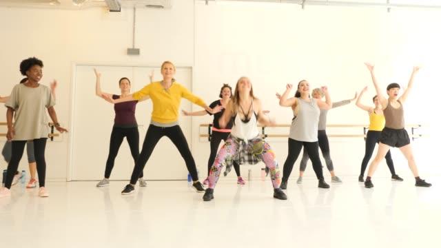 Dancer teaching female students in dance studio