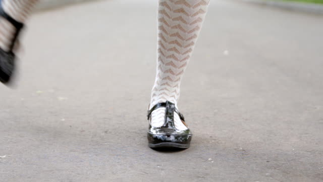 Dancer's legs close-up. Girl dancing solo jazz swing dance on the city's square pavement.