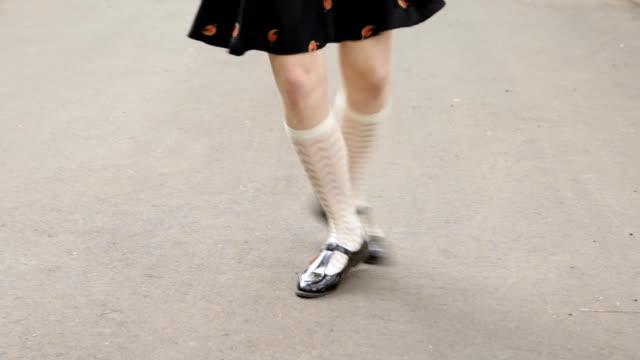 Dancer's legs close-up. Girl wearing white knee socks and black skirt dancing solo jazz swing dance.
