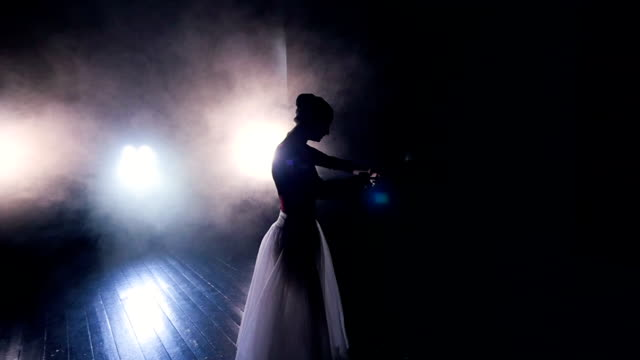 A dancing ballerina comes out from the dark. video