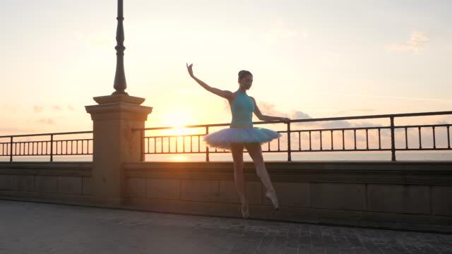 tanzende ballerina in blau ballett tutu und punkt auf seafrontt über wasser bei sonnenuntergang. junge schöne brünette frau üben, stretching und übungen. slow-motion. flare, übersichtsplan - ballettschuh stock-videos und b-roll-filmmaterial