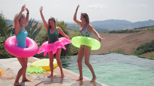 Dancing by the Pool Group of mature female friends at a pool party talking and dancing with inflatable rings. swimwear stock videos & royalty-free footage