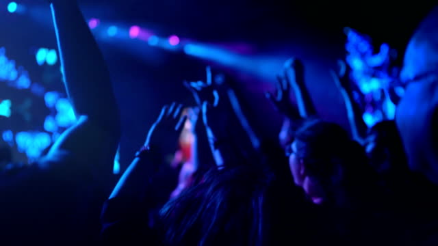 4K Dancing crowd at rock concert with their hands above and cheering