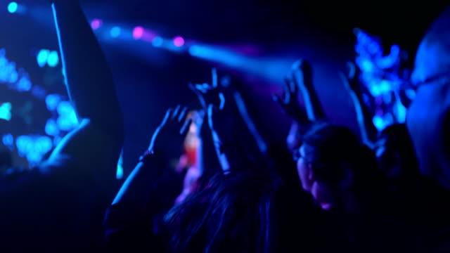 4k tanzendes publikum beim rockkonzert mit den händen oben und jubelnd - live ereignis stock-videos und b-roll-filmmaterial