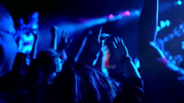 4K Dancing crowd at rock'n'roll gig cheering 4K Dancing crowd at rock'n'roll gig cheering and jumping, flashes of light flickering organized group stock videos & royalty-free footage