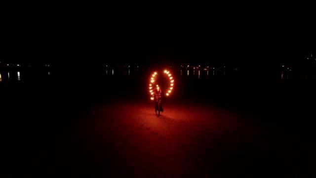 Dancing fire show on the sandbanks beach at sunset
