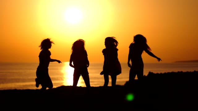 Dancing girls silhouettes at beach sunset. Beach party. Women silhouettes Dancing girls silhouettes at beach sunset. Playful girls enjoying beach party in gloaming. Bachelorette party at seacoast. Tomorrow married. Women silhouettes in evening sunset. Cyprus beach party beach party stock videos & royalty-free footage