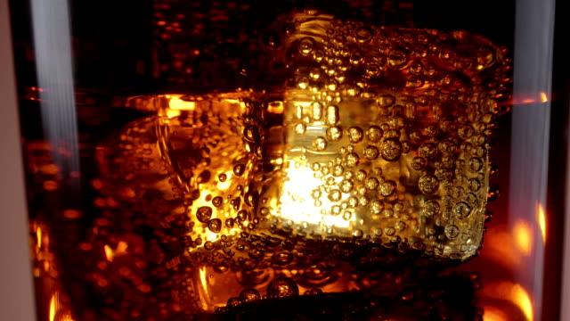 Danse de glace en cubes dans un verre de soude - raffraîchissant Cola froide sur glace - Vidéo