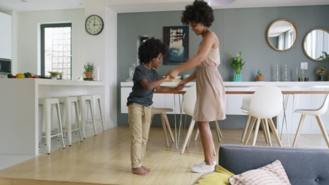 Dancing is in his blood 4k video footage of an adorable little boy dancing on the feet of his mother at home living room stock videos & royalty-free footage