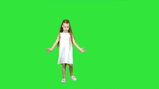 Beetje blond meisje zingen op een groen scherm, Chromakey dansen video