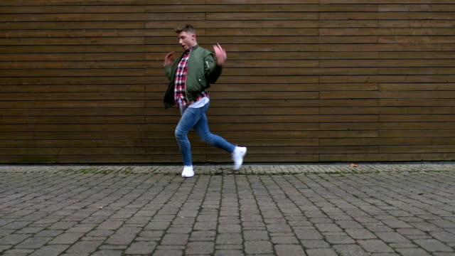 dancing on paved road in front of wooden wall - jeans video stock e b–roll