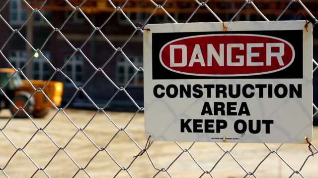 stockvideo's en b-roll-footage met danger keep out sign on fence, construction vehicles working - fence