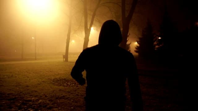 vídeos y material grabado en eventos de stock de hombre de violencia de peligro caminando en la noche brumosa - dureza