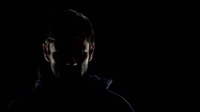 夜暗闇の中、恐ろしいテロ犯罪の準備で危険な匿名男性 - 犯罪者点の映像素材/bロール