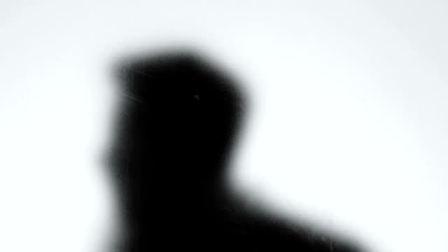 Dangerous criminal shadow looking through glass wall, maniac following victim