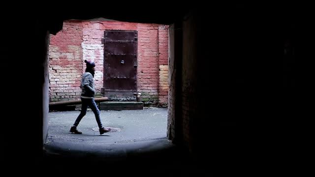 Dangerous deserted place, homeless teenager wandering in abandoned backstreet video