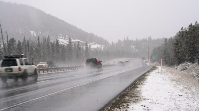 Dangerous driving under the snowfall on the highway in mountains in Colorado