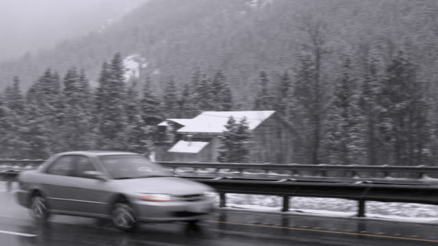 Dangerous driving under the snowfall on the highway in mountains in Colorado, panning camera motion following the car.