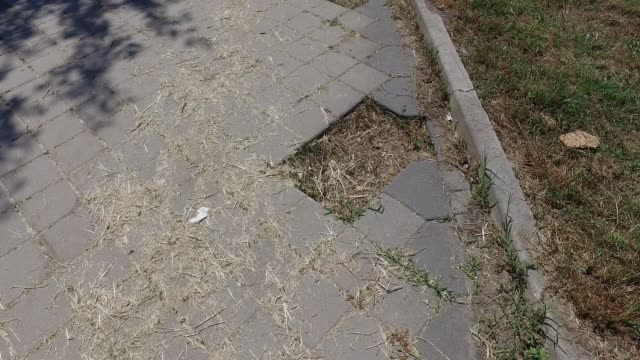 Dangerous hole for pedestrians on damaged sidewalk or pathway with missing block brick in the path