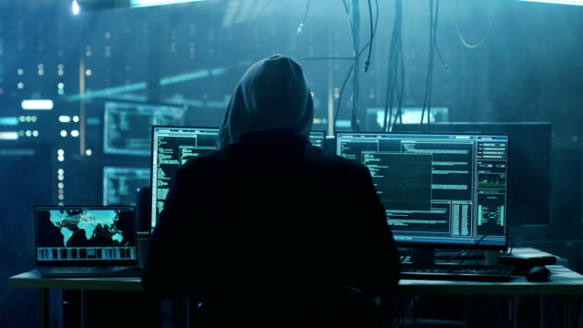 Dangerous Hooded Hacker Breaks into Government Data Servers and Infects Their System with a  Virus. His Hideout Place has Dark Atmosphere, Multiple Displays, Cables Everywhere. Dangerous Hooded Hacker Breaks into Government Data Servers and Infects Their System with a  Virus. His Hideout Place has Dark Atmosphere, Multiple Displays, Cables Everywhere. Shot on RED EPIC-W 8K Helium Cinema Camera. hacker stock videos & royalty-free footage