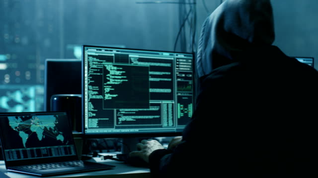 dangerous hooded hacker breaks into government data servers and infects their system with a  virus. his hideout place has dark atmosphere, multiple displays, cables everywhere. - phishing filmów i materiałów b-roll