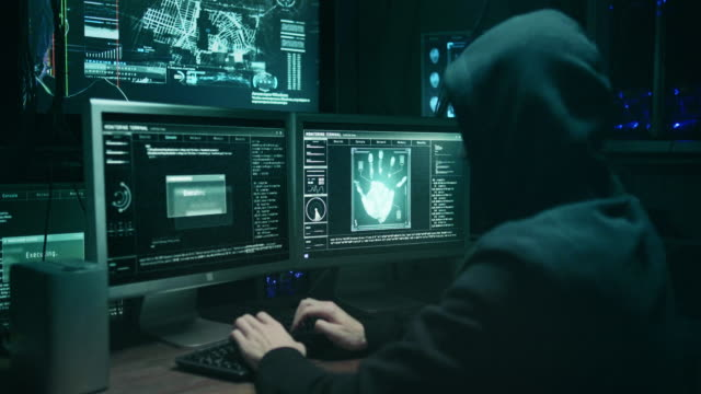 Dangerous Hooded Hacker Breaks into Government Data Servers and Infects Their System with a Virus. His Hideout Place has Dark Atmosphere, Multiple Displays, Cables Everywhere. Dangerous Hooded Hacker Breaks into Government Data Servers and Infects Their System with a Virus. His Hideout Place has Dark Atmosphere, Multiple Displays, Cables Everywhere. hacker stock videos & royalty-free footage