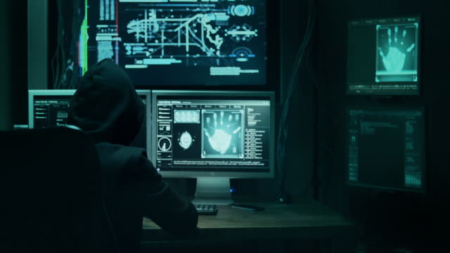 dangerous hooded hacker breaks into government data servers and infects their system with a virus. his hideout place has dark atmosphere, multiple displays, cables everywhere. - anonymous hackers stock videos and b-roll footage
