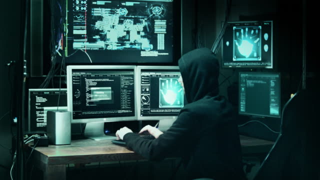Dangerous Hooded Hacker Breaks into Government Data Servers and Infects Their System with a Virus. His Hideout Place has Dark Atmosphere, Multiple Displays, Cables Everywhere. video