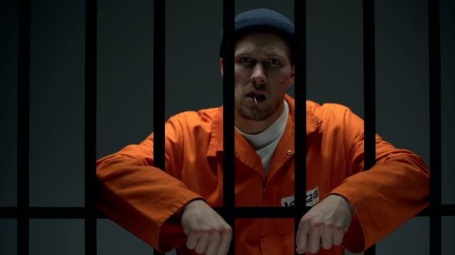 gefährlich inhaftiert kriminelle zahnpicknick auf dem boden und mit der kamera - turngerät mit holm stock-videos und b-roll-filmmaterial