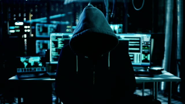 Dangerous Internationally Wanted Hacker with Covered Face Speaks into the Camera. In the Background His Operating Room with Multiple Displays and Cables. video