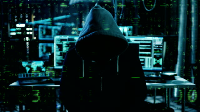 dangerous internationally wanted hacker with covered face speaks into the camera with raining numbers video effect. in the background his operating room with multiple displays and cables. - hacker стоковые видео и кадры b-roll