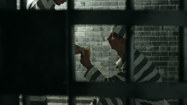 Dangerous prisoner stealing food from other prisoner at prison cell video