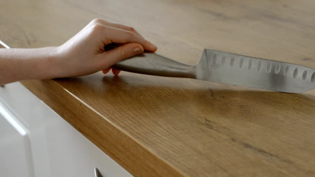 Dangerous situation in the kitchen. Child is playing with kitchen knife. video