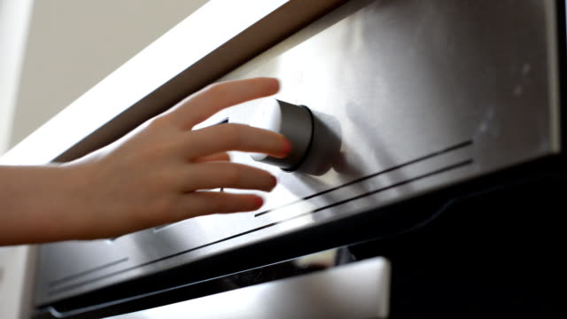 Dangerous situation in the kitchen. Child playing with electric oven. video