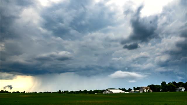 Dangerous storm clouds over a field as it pours down rain