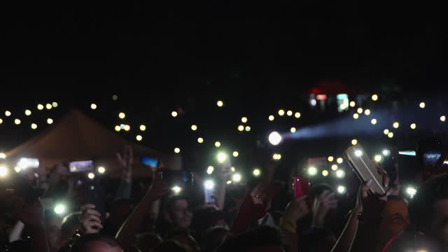 Dark background with concert crowd waving hands with mobile phone lights