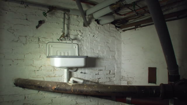 Dark basement with a sink and pipes