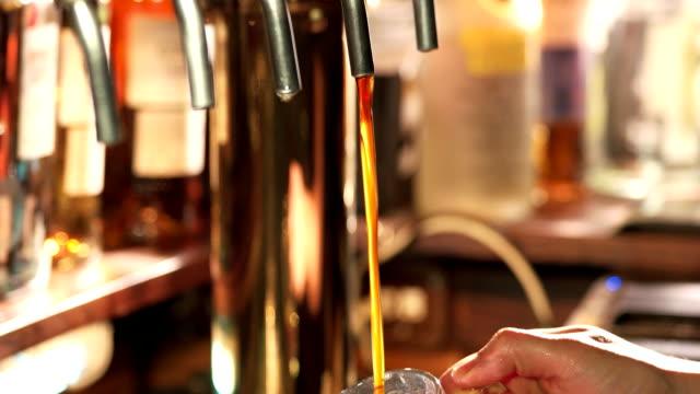 Dark beer filling and overflowing. video
