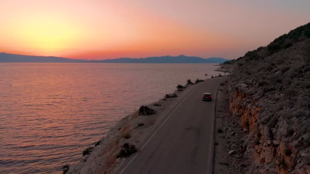 DRONE: Dark colored car drives along the rocky terrain and calm sea at sunset. video