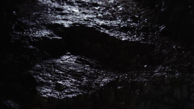 dunkle korridore und wassertropfen fallen in berghöhle - fels stock-videos und b-roll-filmmaterial